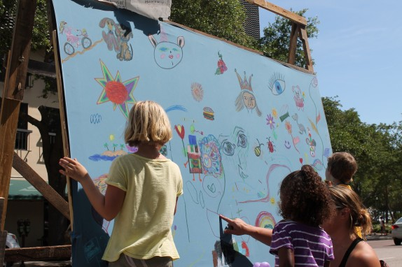 Lily painting a sailboat on a public art project at the Downtown Market