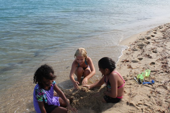 Playing with my new friends. We are burying each other and making mermaid and shark tails.