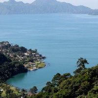 The blue water of Lake Atitlan meets the green volcanic slopes