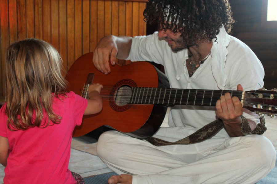 Avi showing Isabella the guitar.