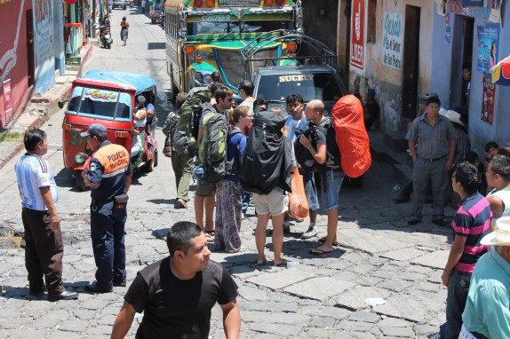 Backpackers frequent the streets of San Pedro. Those with tired feet can usually catch a Chicken Bus such as the one in the background of this pic.