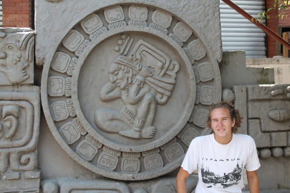 Jake in front of San Juan's carved walls featuring Mayan calendar symbols