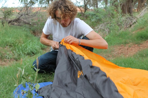 Jake putting up his tent on a grassy creek bank.