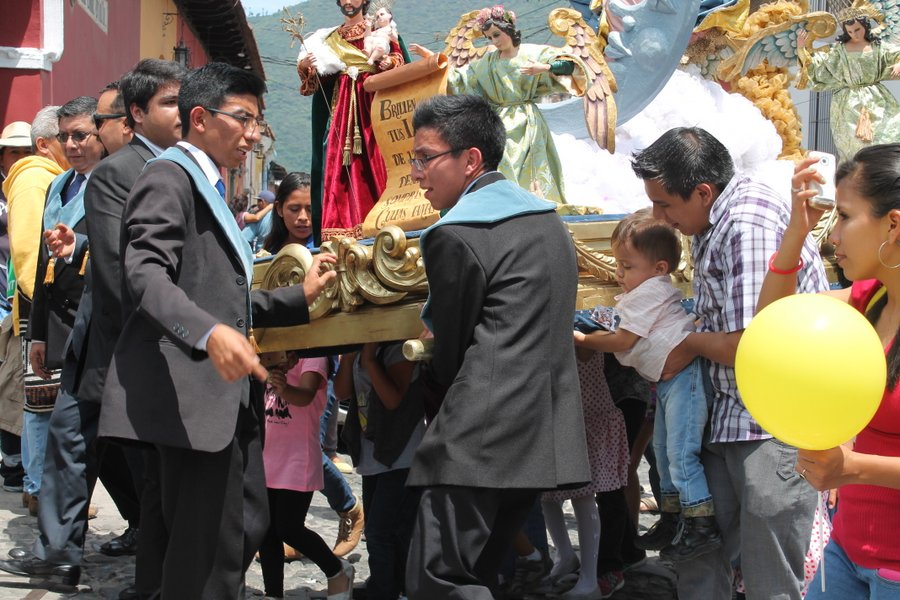 This little boy is lending a helping hand to the religious procession walking through town.