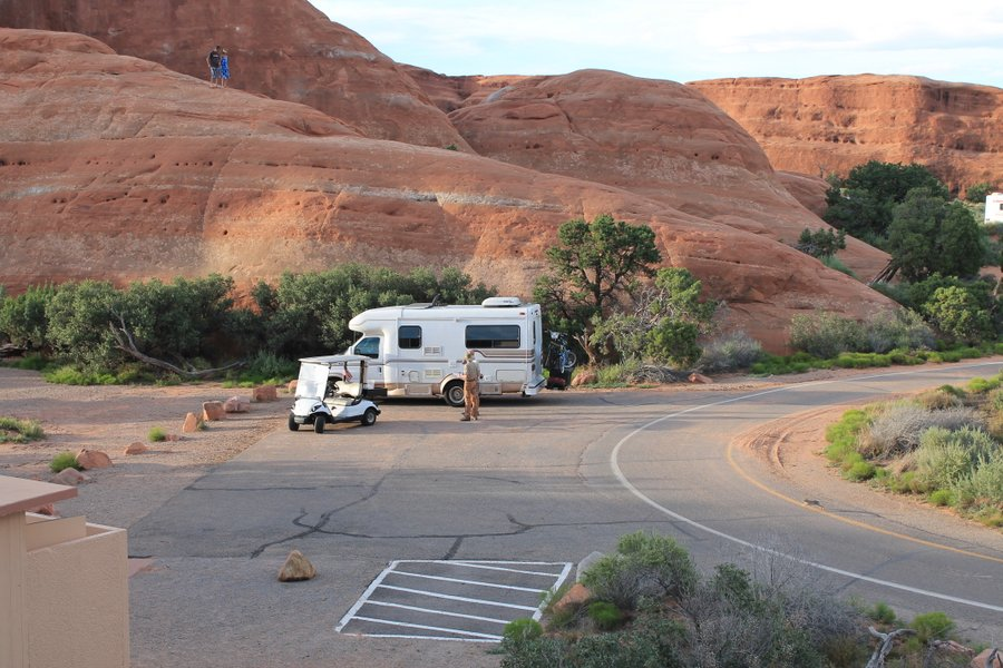 Our little  RV parked at the Arches Campground. Randall and the Ranger are discussing the terms of our use of the group parking area.