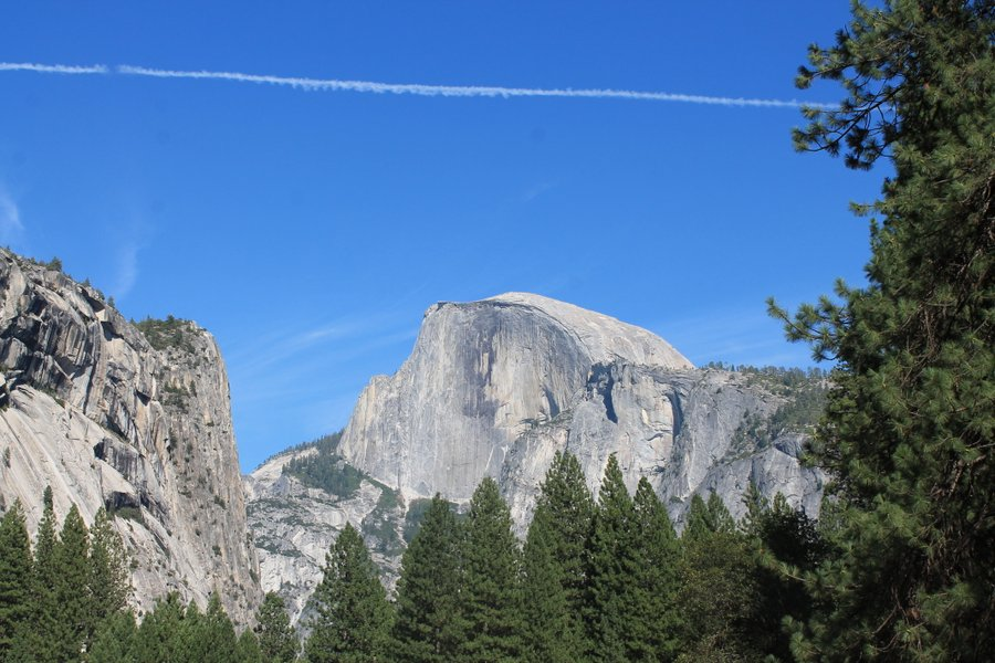 Half Dome with a contrail overhead.