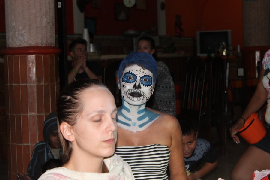 The lady in the foreground is sitting to get her face painted while the one in back just got all finished up.