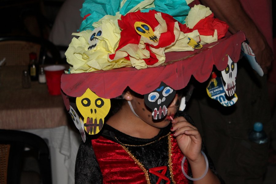 "Close-up on one of the Thriller dancers taking a candy break. Big hats are also part of the ""Katrina"" style costumes. Katrinas are skinny skull-like paper machete figures which are made for the weekend."