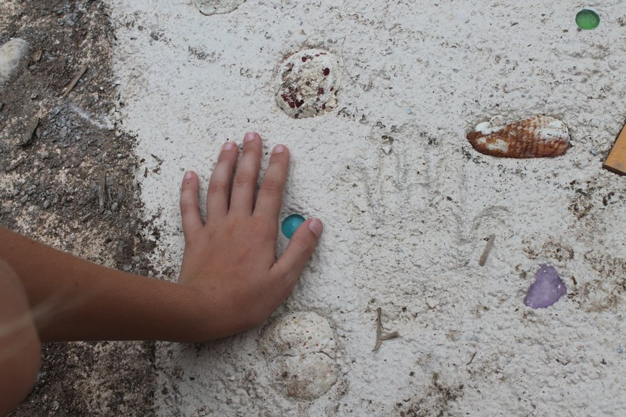 Lily's faint handprint in the El Milagro sidewalk. The sidewalk is also adorned with shells and glass beads.